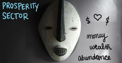 """Photograph of a frankly creepy black and white wooden mask. It has narrow eyes and black teeth.  Around the mask the words are written """"Prosperity Sector. money, wealth, abundance"""""""
