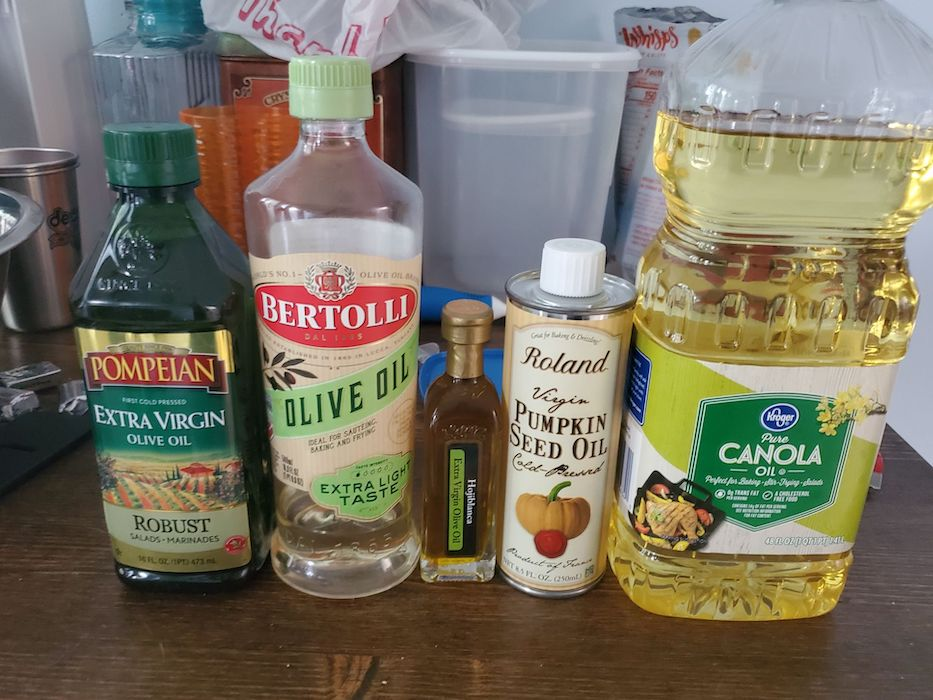 Five cooking oils of varying sizes are lined up on a counter. In order they are Pompeian Robust Extra Virgin Olive Oil, Bertolli Extra Light Taste Olive Oil, Hojiblanca Extra Virgin Olive Oil, Roland Cold-Pressed Virgin Pumpkin Seed Oil, and a gigantic bottle of Kroger Pure Canola Oil.
