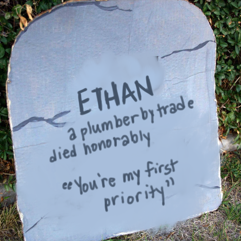 """Photo taken from the internet of a cardboard grave stone someone made for Halloween as a craft. The original words have been expertly scrubbed off by Sneer Campaign's resident artist, Amandoll, and written in their place are the words: """"Ethan. A plumber by trade. Died honorably. Quote: """"You're my first priority."""""""""""